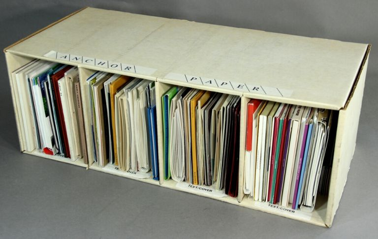 A collection of approximately 65 paper sample books in a custom cardboard Anchor Paper Company bookshelf